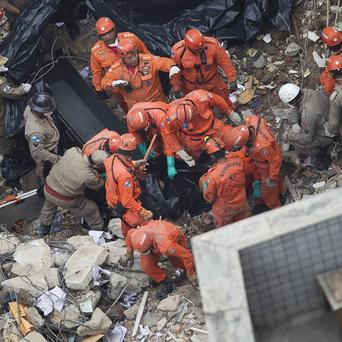 Rescue workers amid the rubble after a building collapsed in Rio de Janeiro, Brazil (AP)