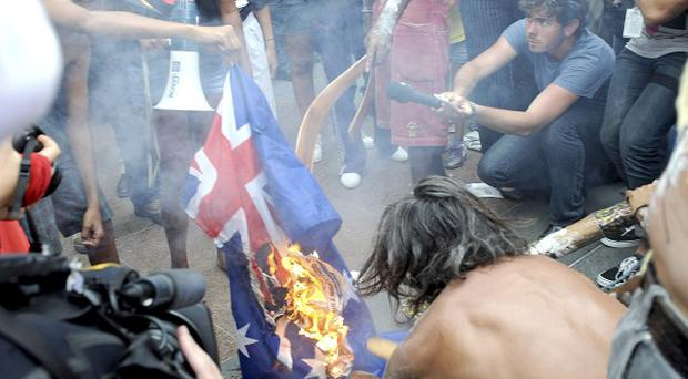 Aboriginal protesters burn an Australian flag during a protest outside Parliament House in Canberra (AP)