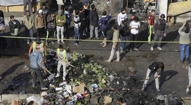 People gather at the scene of a car bomb attack in Zafaraniyah, Baghdad (AP)