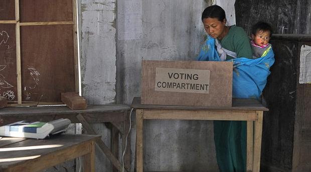 A woman with her child casts her vote at a polling station in Thoubal constituency on the outskirts of Imphal, India (AP)