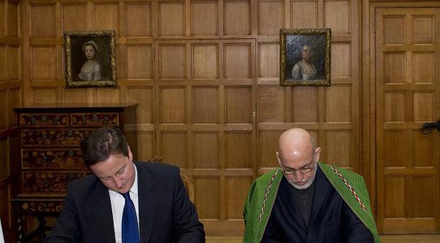 Prime Minister David Cameron, left, and President Hamid Karzai of Afghanistan sign the agreement