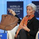 IMF managing director Christine Lagarde shows her bag as she speaks during a session at the World Economic Forum in Davos, Switzerland (AP)