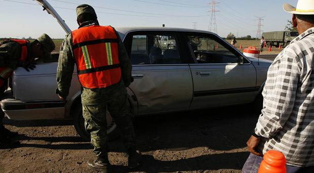 Mexican army soldiers inspect a car at a checkpoint during a drugs crackdown near the country's northern border (AP)