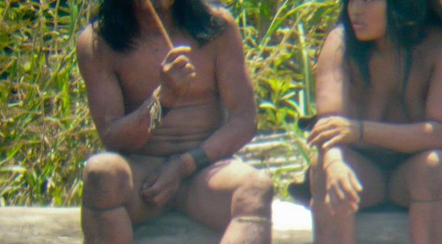 Mashco-Piro Indians sit on a log next to a river (D Cortijo/Survival International/uncontactedtribes.org)