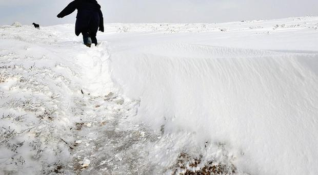 A woman negotiates deep snow on Dunkery Hill on Exmoor, Somerset