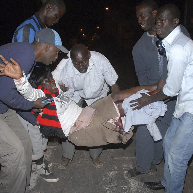 Men carry a woman injured during protests in Dakar, Senegal (AP)