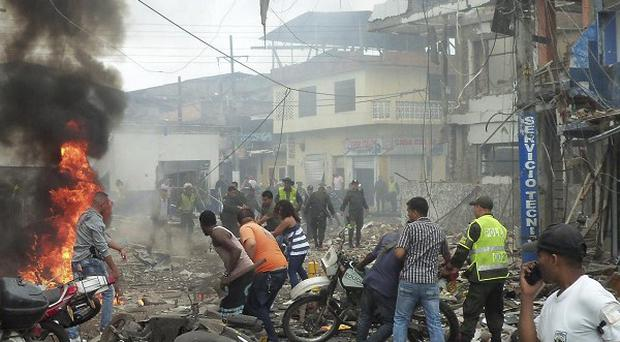 Residents and police rush to the site where a bomb exploded outside a police station in Tumaco on Colombia's southern Pacific coast (AP)