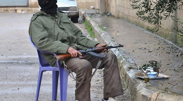 A rebel guards an alley, at Rastan area in Homs province, central Syria (AP)