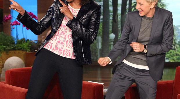 First Lady Michelle Obama dances with TV host Ellen DeGeneres, before the pair began a press-up challenge (AP/Warner Bros)