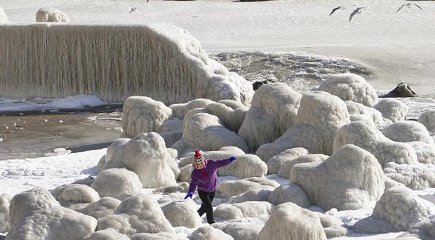 A child walks between stones covered in ice as the waters of the Black Sea froze near the shore in Constanta, Romania (AP)