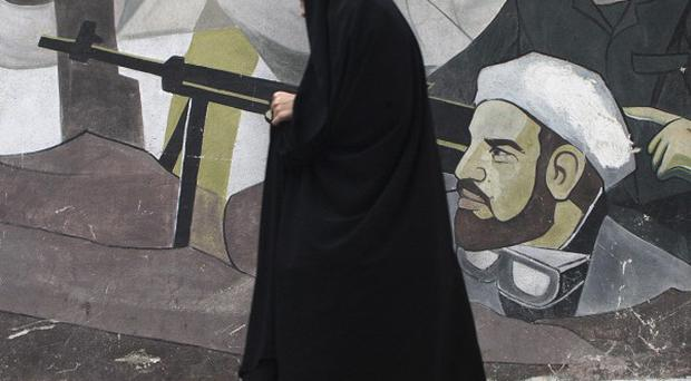 A veiled Iranian woman walks past a mural depicting members of Basij paramilitary force, portraying Iranians' solidarity against their enemies (AP)