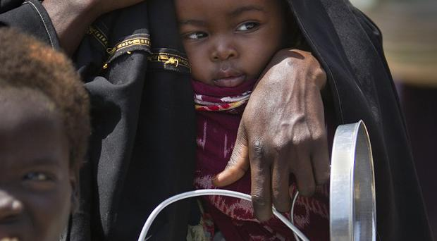 A mother holds her baby and an empty container as they queue at a food distribution centre in Somalia(AP)