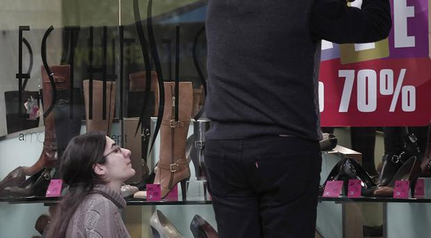 Shop workers take down sales signs on Athens' main commercial Ermou Street (AP)