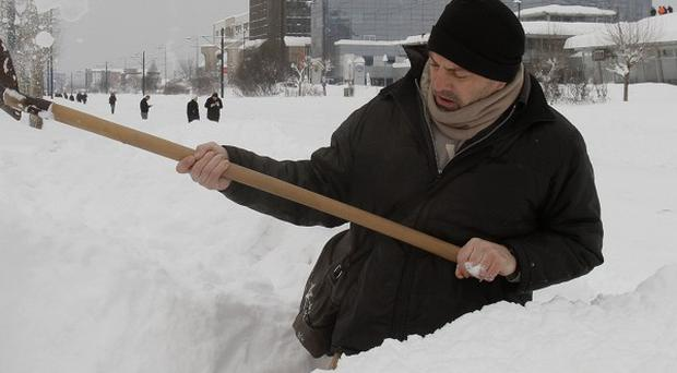 A Bosnian man shovels deep snow to clear the path for pedestrians, in the Bosnian capital of Sarajevo (AP)