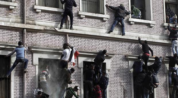 Protestors climb the exterior of a building during clashes with security forces near the interior ministry in Cairo, Egypt (AP)