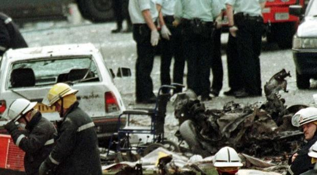 Police officers and firefighters inspect the damage caused by the bomb explosion in Market Street, Omagh, in 1998
