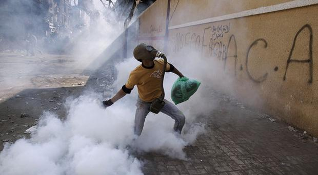 A protester wearing a gas mask throws away a tear gas canister fired by security forces in Cairo (AP)