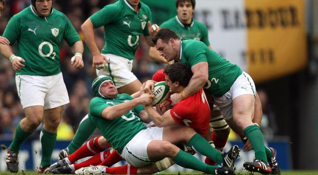 Ireland's Rory Best and Cian Healy tackle Sam Warburton of Wales