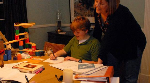 Parenst say work or household chores prevents them helping their children with homework, according to a survey (AP)