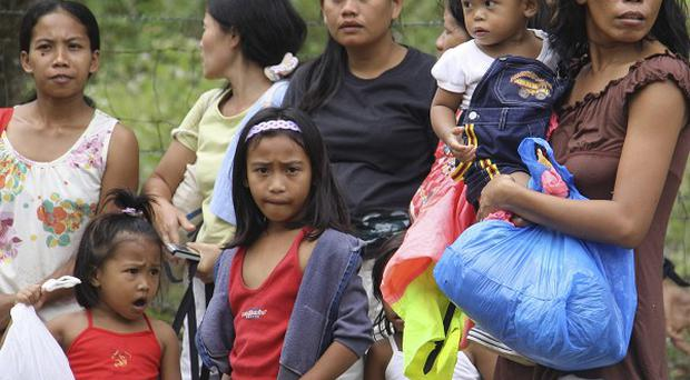 Residents stand in the open after a large earthquake struck just off Negros Island (AP)