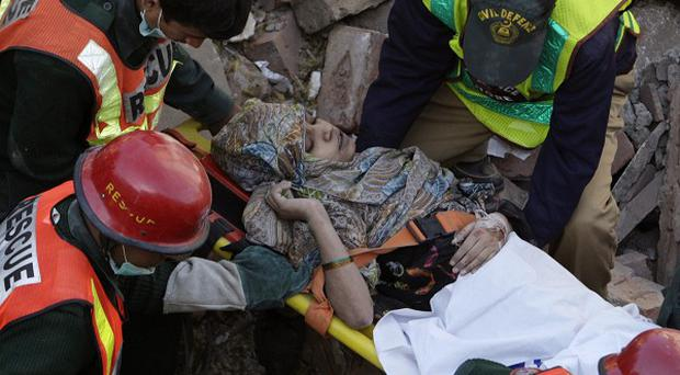 Rescue workers carry a woman who was recovered from the debris of a collapsed building in Lahore, Pakistan (AP/KM Chaudary)