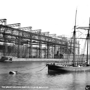 Titanic. The Great gantry, Queen's Island, Belfast. This photograph shows the enormous scale of the ship, together with the complex structure of the enfolding steel gantry, from which she will soon be free. The photograph also reflects old and new maritime technologies, with the traditional wooden schooner in the foreground contrasting eith the modernity ot Titanic. Photograph © National Museums Northern Ireland. Collection Harland & Wolff, Ulster Folk & Transport Museum