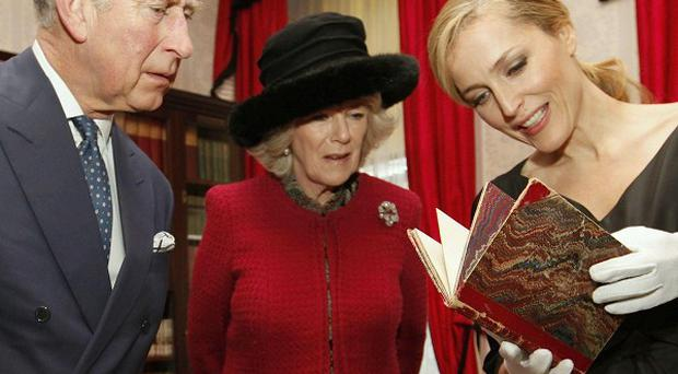 Actress Gillian Anderson shows a first edition of a Charles Dickens book to the Prince of Wales and the Duchess of Cornwall