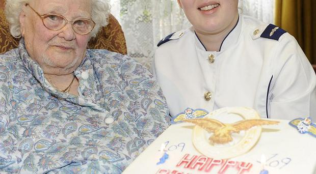 Florence Green seen on her 109th birthday being presented with a cake by LAC Hannah Shaw on behalf of the RAF at her home in King's Lynn, Norfolk