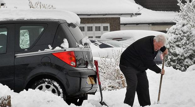 A householder digs his car out of snow at Ingatestone, Essex