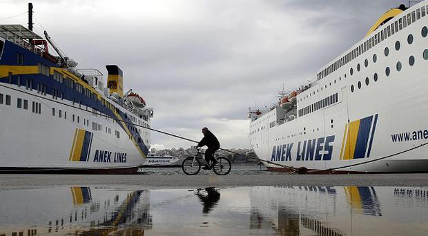 A man on a bicycle passes docked ferries in a port near Athens during a strike staged in response to new austerity measures (AP)