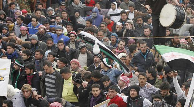 Anti-regime protesters hold a demonstration in Idlib, Syria (AP)