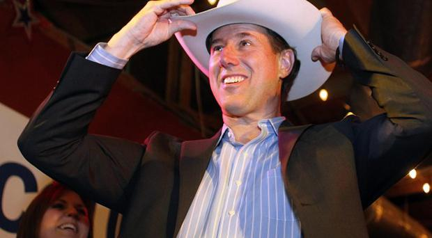 Rick Santorum puts on a cowboy hat after meeting with supporters at a rally in Plano, Texas (AP/Sharon Ellman)
