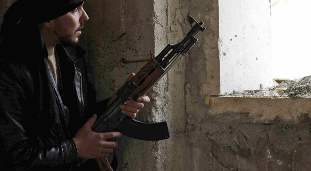 A Syrian rebel peers through a window in Idlib, as Government forces step up their attacks(AP)