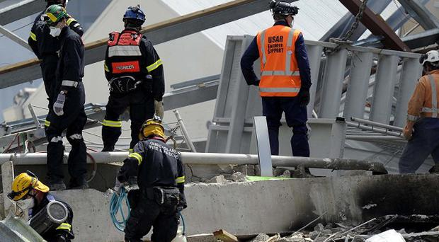 Recovery personnel working on the destroyed CTV building in Christchurch after last year's earthquake(AP)