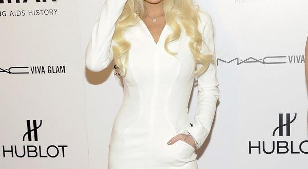 Lindsay Lohan wore a conservative white dress for the amfAR event
