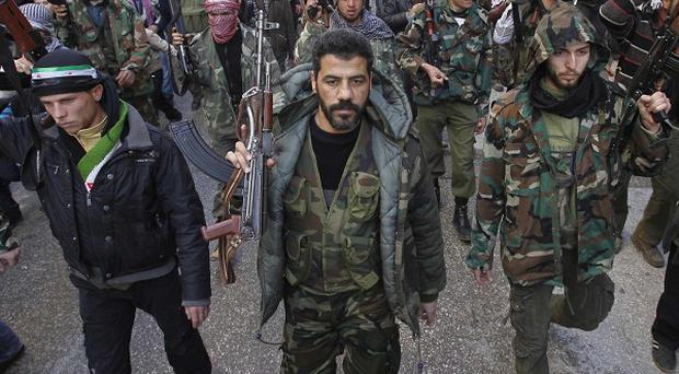 Syrian rebels march in a show of strength during a demonstration in Idlib (AP)