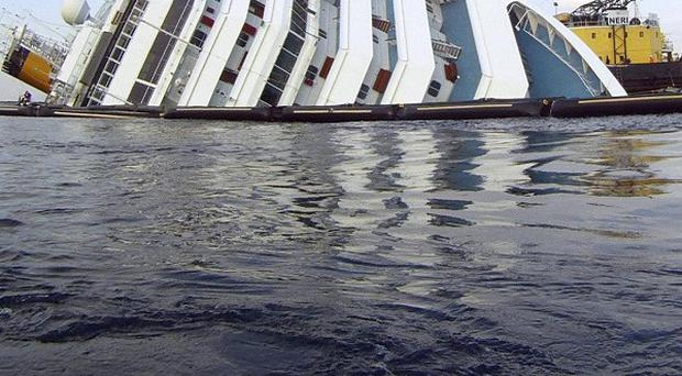 The cruise ship Costa Concordia ran aground off the Tuscan island of Giglio, Italy, a month ago (AP)
