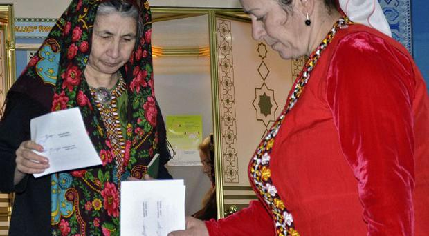 Turkmen women dressed in traditional costume cast their ballots at a polling station in Ashgabat (AP)