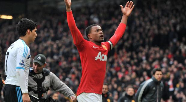 Manchester United's Patrice Evra celebrates victory as Liverpool's Luis Suarez walks off during the Barclays Premier League match at Old Trafford, Manchester