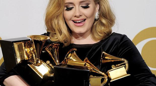 Adele poses backstage with her six Grammy awards (AP)