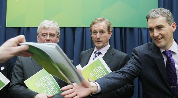 Taoiseach Enda Kenny with Tanaiste Eamon Gilmore, centre, and TDs John Perry, left, and Tom Barry in Leopardstown, Dublin