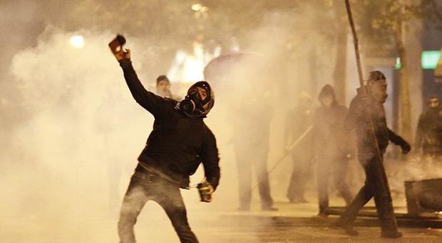 An anti-cuts protester throws an object towards riot police during clashes in Athens (AP)
