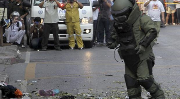 A bomb disposal expert examines the scene of two bomb explosions in Bangkok, Thailand (AP)