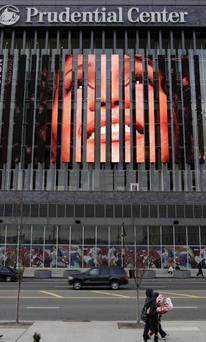 People walk past, a large image of Whitney Houston displayed on the side of the Prudential Center in Newark, N.J., Tuesday, Feb. 14, 2012.
