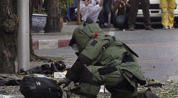 A Thai explosives officer examines a backpack that was left on the bomb site in Bangkok (AP)