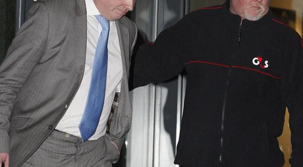 Rangers owner Craig Whyte leaves Ibrox Stadium in Glasgow with a security guard