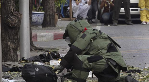 A Thai bomb disposal expert examines a backpack dropped by one of the bombers (AP)