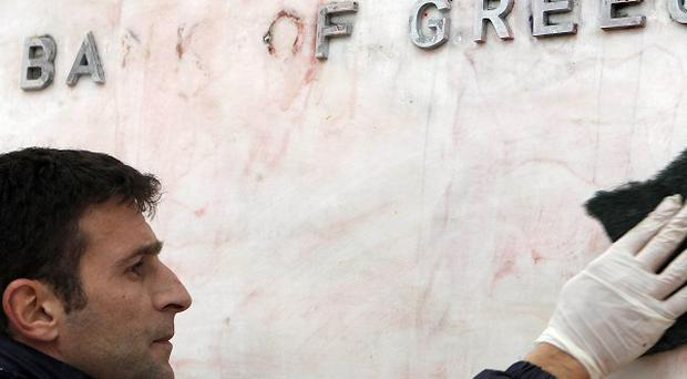 A worker cleans the sign of the Bank of Greece from red and black paint after riots in Athens (AP Photo/Thanassis Stavrakis)