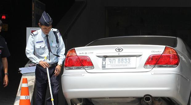 A Thai security guards inspect a car entering a building which houses the Israeli Embassy in Bangkok (AP)