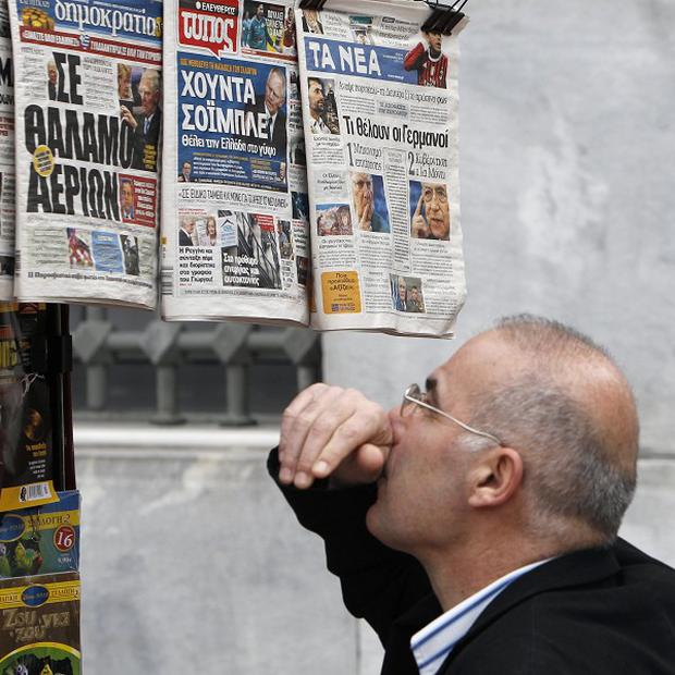 A man reads the front pages of three Greek newspapers critical of German Finance Minister Wolfgang Schaeuble(AP)